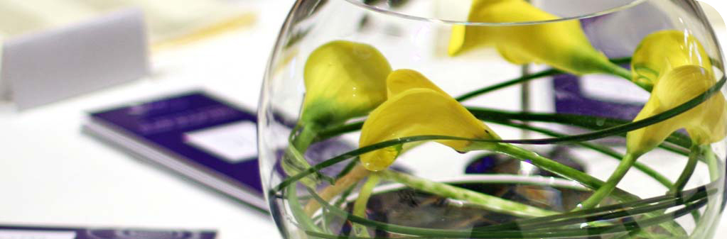 yellow-calla-lilies-and-still-grass-in-a-fish-bowl-glass-vase